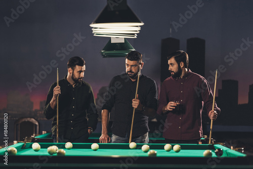company of successful handsome men standing beside pool table with drink at bar