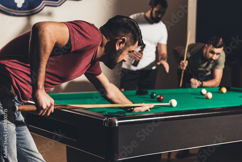 company of handsome men playing in pool