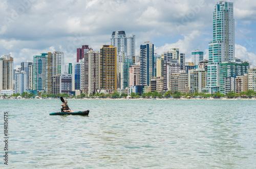 Poster Chicago Jovem mulher loira passeando de caiaque em praia do brasil com prédios no fundo, praia e metrópole