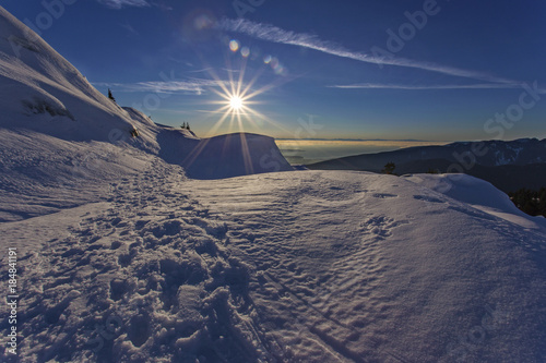 Foto op Plexiglas Canada Scenic winter sunset landscape on snowy mountain Seymour above Vancouver British Columbia with snowshoe tracks and distant Burrard Strait and Vancouver Island on the horizon
