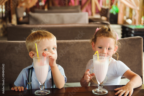 Papiers peints Lait, Milk-shake Little boy and girl drinking milkshakes in a cafe outdoors.