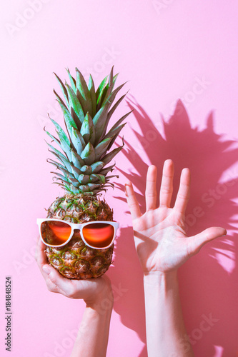 Creative layout made of summer tropical fruits and leaves. Pineapple in glasses on a woman hand. Five fingers. pink isolated bacground. Flat lay. Food concept. - 184848524