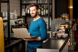 Handsome man in blue sweater working with laptop at the bar of the modern cafe interior - 184849501