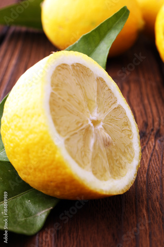 Poster Pile of lemons with leaves on brown wooden table