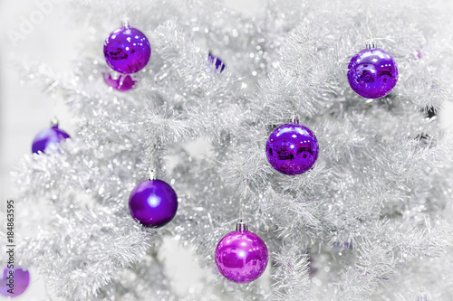 Decoration ultraviolet baubles on silver artificial Christmas tree