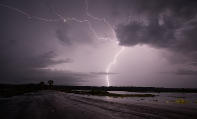 Lightning strike at Fogg Dam, Northern Territory, Australia against a cloudy purple sky