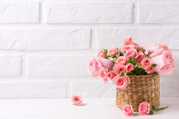 Background with pink roses flowers against white brick wall.