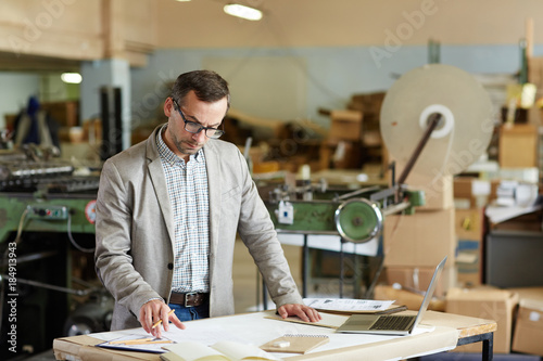 Foto Murales Mature engineer in smart casual looking at one of technical sketches at work