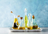 different shapes, types and sizes of cruets with olive oil on the table on a tray on blue - 184947917