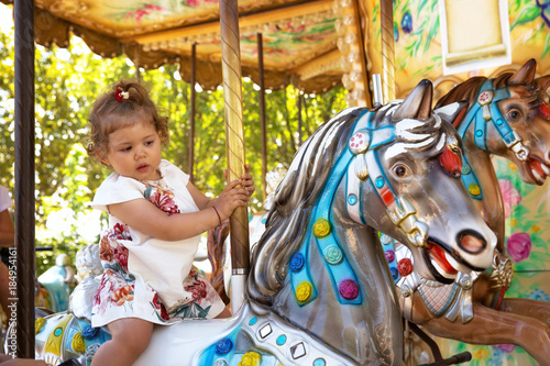 Poster Happy female toddler ridding colorful carousel horse.