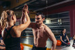 Smiling men and women doing high five in gym. making high five gesture in gym after workout