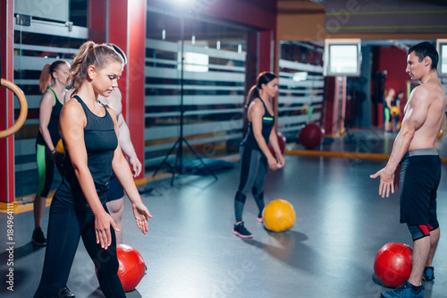 Tuinposter Gymnastiek Group of six attractive young male and female adults doing pull ups on bar in cross fit training gym