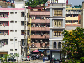 Kuala Lumpur, Malaysia - Circa October 2017: A view of the street and old apartment buildings with many air conditioners in Kuala Lumpur