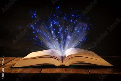 image-of-open-antique-book-on-wooden-table-with-glitter-overlay