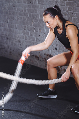 vertical photo of athletic woman wearing red pants and black top doing some cross fit exercises with battle rope indoor