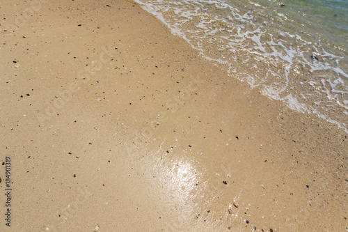 Sea surf on the beach with sand.