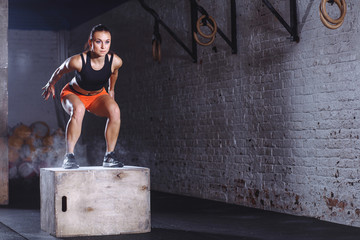 young woman jumping box and talc powder departs from under feet. Fitness woman doing box jump workout at cross fit gym.