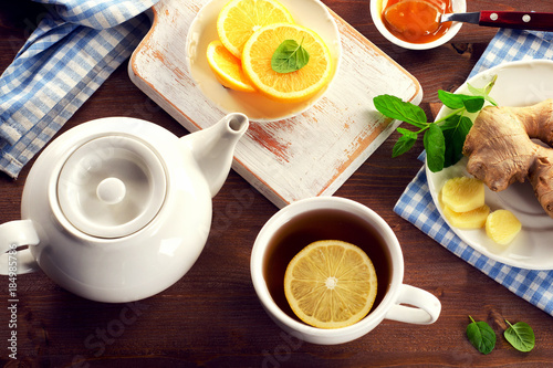 Poster Tea with lemon, ginger, honey  and mint on a wooden background