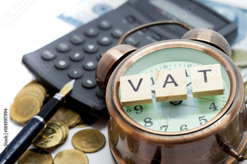 VAT word on Alarm clock and stacks coins on white table, Success in business concept.