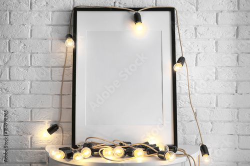 Mockup of blank frame with garland on table © Africa Studio
