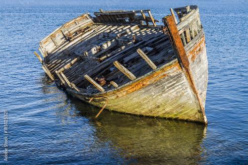 Foto op Plexiglas Schipbreuk vieux bateau en bois abandonné brisé sur la mer - transport arrière plan