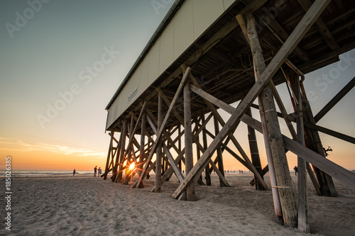Foto op Plexiglas Noordzee Nordseeurlaub -Sonnenuntergang am Strand von St. Peter Ording, typischer Stelzenbau aus Holz