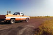 An old pickup truck riding along a farm road with a ranch and horses on the background at sunset in rural Texas, USA; Concept for travel in Texas and in the USA