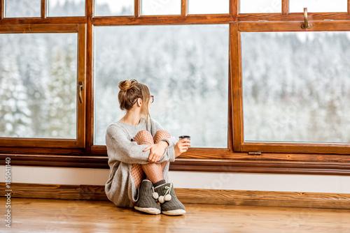 Młoda kobieta w sweter siedzi w pobliżu duże okna w przytulnym drewnianym domku z pięknym widokiem krajobraz w czasie zimy
