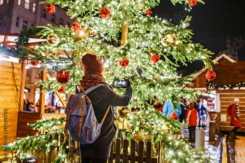 Woman tourist at night admiring the Christmas tree with lights in the main squar Poster