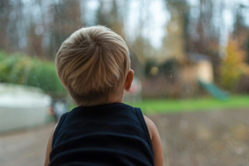 Single toddler child staring out of a window