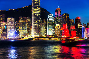 Skyline of Hong Kong at night with red boat