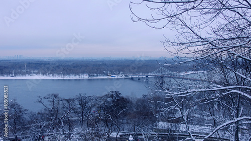 Foto op Plexiglas Kiev Winter landscape. View from above on the Dnieper River in Kiev. Trees in the snow above the mountain. The Left Bank of Kiev