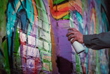 cropped view of street artist painting graffiti with aerosol paint on wall at night - 185086941