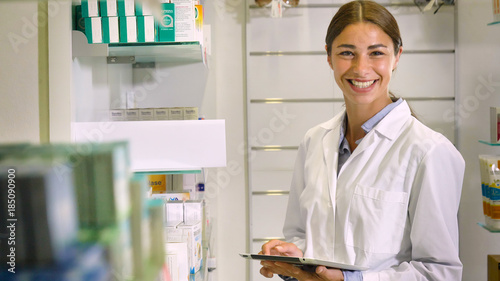Poster Apotheek Portrait of a beautiful young girl (woman) pharmacist, consultant, working at a pharmacy, selling and checking medication, smiling, giving advice. Concept: profession, medecine, medical education.