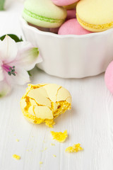 Bitten macaroon on a wooden table with flowers