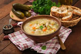 Soup with pickled cucumbers and pearl barley - rassolnik on a wooden background. - 185100588