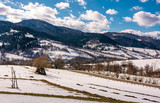 spring is comming. last days of winter landscape. rural field with weathered yellow grass covered with snow. village at the foot of the mountain ridge - 185146741