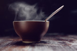 brown steaming bowl of hot meal with spoon on wooden table close up - 185147382
