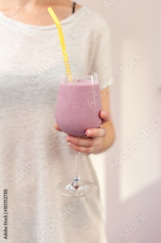 Foto op Canvas Milkshake Woman holds a glass with pink cocktail