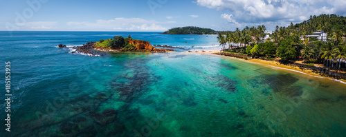 Fotobehang Panoramafoto s Aerial panorama of the tropical beach and clear sea with coral reefs in the town of Mirissa, Sri Lanka