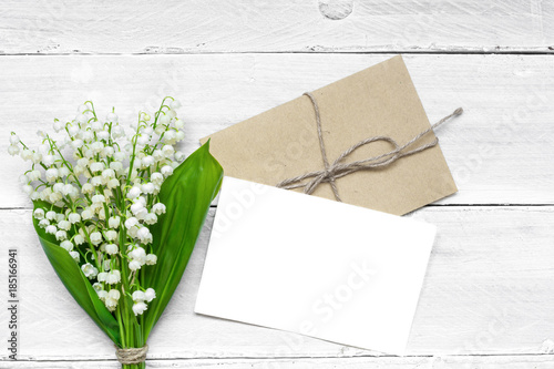 Foto Spatwand Lelietjes van dalen blank white greeting card and envelope with spring lily of the valley flowers