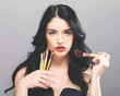 Beautiful young woman holding makeup brushes on a solid background