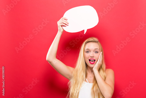 Young woman holding a speech bubble on a solid background Poster