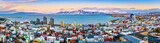 Aerial panorama of downtown Reykjavik at sunset with colorful houses and snowy mountains in the background - 185205956