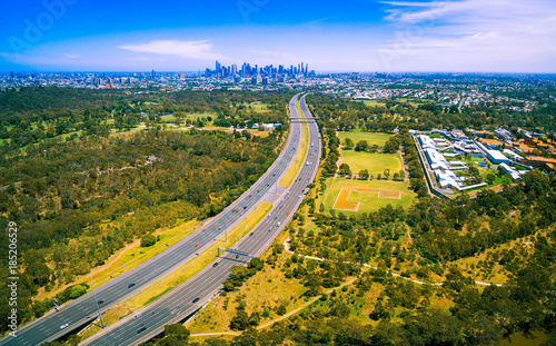 Fotobehang Honing Aerial panorama of green parkland, Melbourne Polytechnic, and Melbourne CBD skyscrapers in the distance on summer day