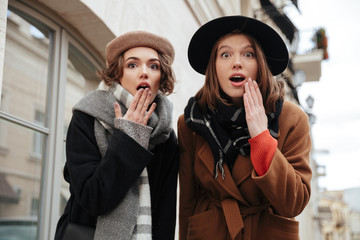 Portrait of two surprised girls dressed in autumn clothes