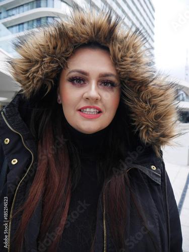 Uśmiechnięta kobieta w zimie na tle budynków