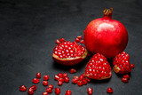 Pomegranate and seeds close-up on dark concrete background - 185225171