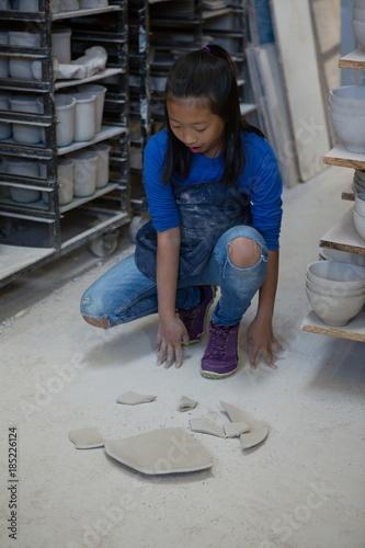Foto Murales Girl looking at broken pieces of plate