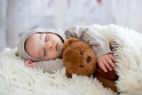 Sweet baby boy in bear overall, sleeping in bed with teddy bear